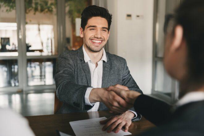 Mann schüttelt Hände während eines Bewerbungsgesprächs
